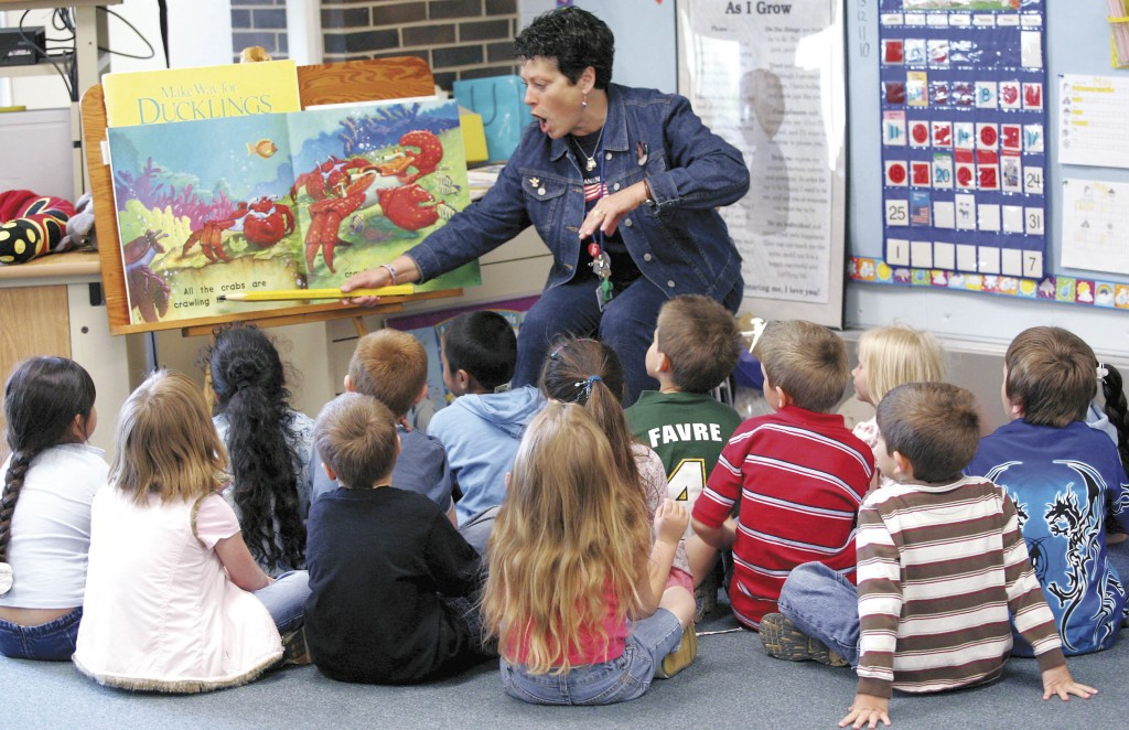 "Madison Elementary kindergarten teacher Kathie Koebler reads the book ""Splash in the Ocean"" to her Janesville School District students in May. Some of the students have never had a book read to them before they got to the school. Photo Courtesy of THE JANESVILLE GAZETTE"