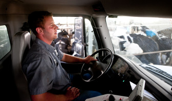Jeremy Meissner drives a feed truck through his dairy barn at Norm-E-Lanes farms in Chili, Wis., on July 12, 2012.