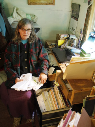 Prisoner rights advocate Peg Swan, in her home office, with letters from inmates at Waupun Correctional Institution. She says she has been hearing for about a year about high lead levels in the water at the 150-year-old prison.