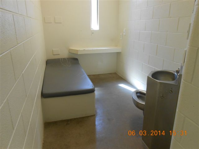 An unoccupied cell in the segregation unit at Waupun Correctional Institution. The cells are small, with a narrow window and concrete and steel furnishings.