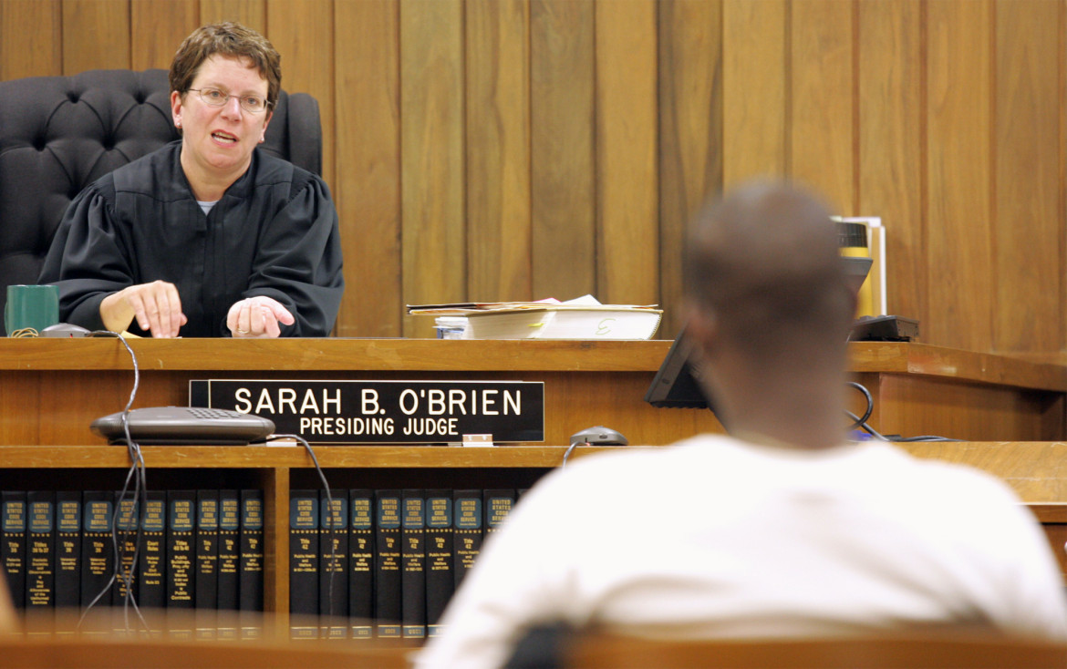Dane County Circuit Judge Sarah O'Brien speaks to a graduate of the drug court program before awarding his diploma in this 2005 photo. O'Brien ran the specialty court in Madison until her retirement in 2012. She says participants have been disproportionately white, a disparity the court is attempting to address.