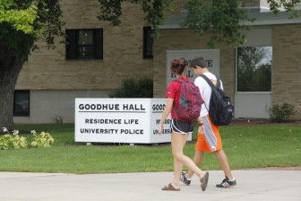 Students pass in front of Goodhue Hall, which includes the University of Wisconsin-Whitewater police department. The campus is one of three UW System four-year campuses that acknowledge using students to buy drugs from others in controlled buys. Photo shot Sept. 5, 2014.