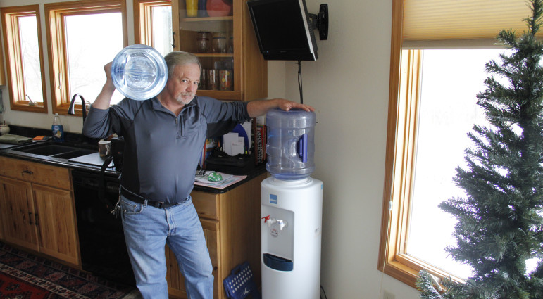 Frank Michna stands with the water bottles he buys to replace his tainted well water in Caledonia.