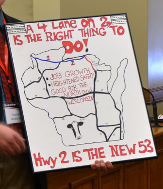 A Superior Days representative holds a sign advocating for an expansion of Highway 2 from a two-lane to a four-lane highway. Local economic development leaders say businesses interested in the region often require a four-lane highway in the area, which hurts economic growth.