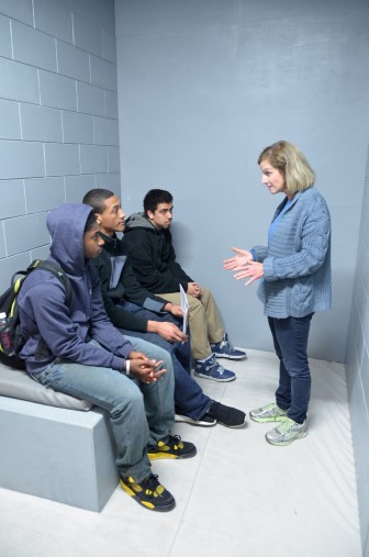 The statewide faith-based group, Wisdom, commissioned construction of this mock-up of an isolation cell for its campaign against solitary confinement. Here, Wisdom volunteer Jane Miller talks with students visiting the cell at Marquette University in March.