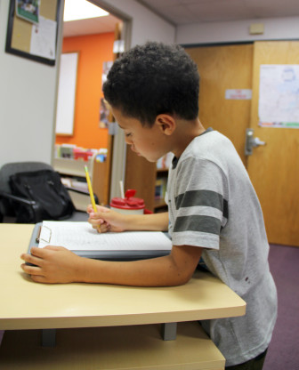 Third-grader Damare McCollum signs in to use a computer after school at the Packer Townhouses community learning center in Madison.