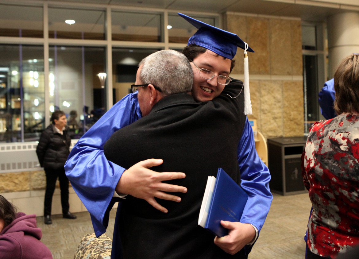 Ien Roder-Guzman, 24, hugs his dad Scott Roder after Madison College's graduation ceremony in December.