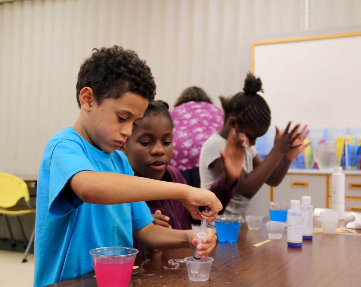 T'Asia Mondie, grade 5, looks over third-grader Damare McCollum's project during a weekly Science Club meeting at the Packer Townhouses community learning center in Madison.