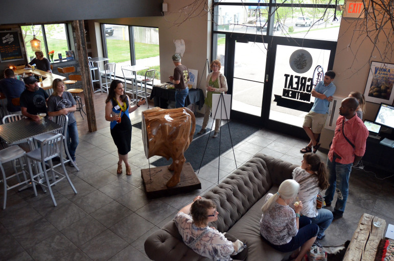 "WCIJ multimedia director Kate Golden explains the significance of the cow-shaped art piece ""A Day in Brown County"" to an audience at Great Northern Distilling in Plover, Wisconsin on May 7, 2015. The exhibit was part of the ""Investigative Reporting + Art"" tour put on by Carrie Roy and WCIJ."