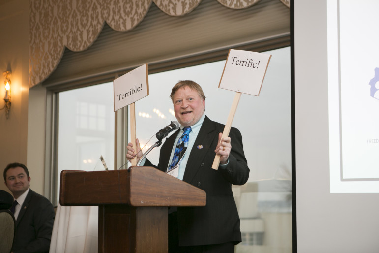 """Bill Lueders, president of the Wisconsin Freedom of Information Council, holds up signs while recapping highlights and lowlights from the state's past year in open government at the Wisconsin Watchdog Awards. Lueders also awarded the Council's annual Openness Awards, or """"Opees."""""""