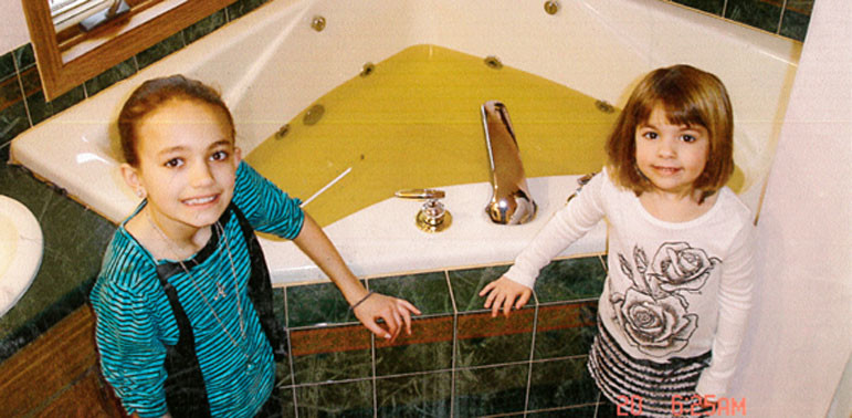 Chuck Wagner's granddaughters, Mackayla, left, and Maggie DeBaker, pose with polluted well water from his Kewaunee County home around 2010. In 2013, Wagner had a new, deeper well drilled at a cost of $10,000. The new well has also become polluted with viruses from cattle manure, and he now uses a reverse osmosis system to filter the water before drinking or cooking.
