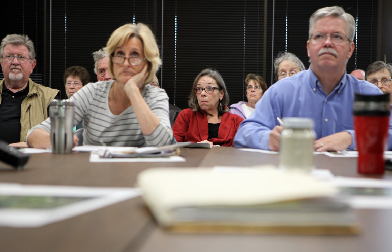 Kathy Kachel, center, a Wisconsin homeowner whose house overlooks Pattison Sand Co.'s Iowa operations, reacts to testimony given by University of Iowa professor Patrick O'Shaughnessy at a meeting of the Mine Reserve Expansion Study Committee in Elkader, Iowa. In the foreground are committee members Anne Osmundson and Tom Blake.