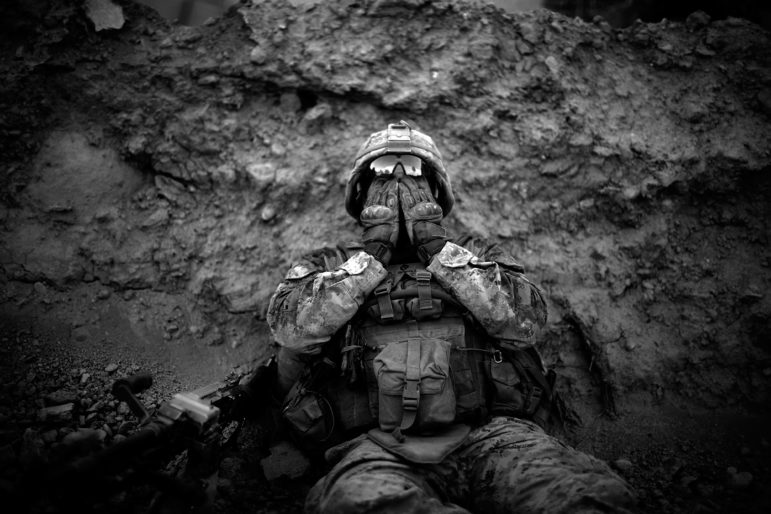Marine Lance Cpl. Anthony Espinoza wipes the sweat out of his eyes at the end of a daylong patrol out of the Sangin District in southern Afghanistan in May 2011.