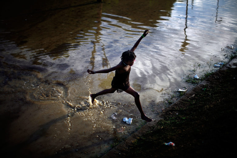 A little girl jumps across a flooded field containing the sewage runoff from the Mais Gate Camp after heavy rains in Port-au-Prince. Quake survivors were trying to stay dry and dig out of the mud in the tent camps of the Haitian capital, a warning of fresh misery for the 1 million homeless living in the streets and in IDP camps one month after the devastating earthquake.