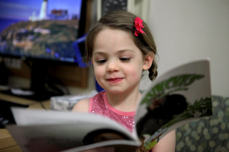 Naja Tunney, 5, reads a book at the Group Health Cooperative health care center in Madison, Wis., while her sister, Hannah, 2, gets a check-up. GHC participates in the national Reach Out and Read program, which distributes distributes books to children up to age 5 at each regular check-up. The program is designed to encourage families to develop good reading habits.
