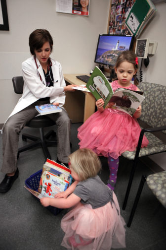 Francesca Vash, a nurse practitioner at Group Health Cooperative health care center in Madison, Wis., interacts with her patients Naja Tunney, 5, and her sister Hannah, 2, during a check-up. GHC participates in the national Reach Out and Read program, which distributes distributes books to children up to age 5 at each regular check-up.
