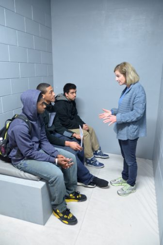 The statewide faith-based group, Wisdom, commissioned construction of this mock-up of an isolation cell for its campaign against solitary confinement. Here, Wisdom volunteer Jane Miller talks with students visiting the cell at Marquette University in March 2015. Wisdom is supporting the Wisconsin inmate hunger strike aimed at eliminating administrative confinement, a status in which prisoners are allowed to be held in solitary confinement for prison safety reasons indefinitely.