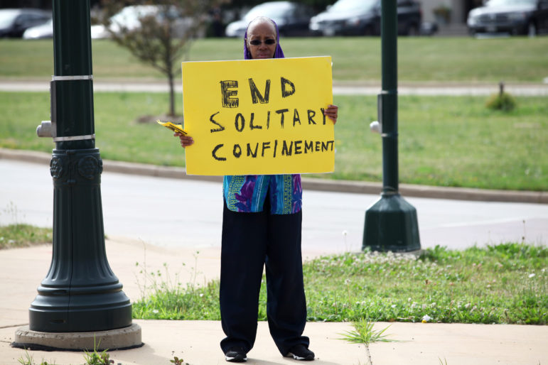 Sister Linda Muhammad holds a sign during a rally outside the state Department of Corrections headquarters in Madison, Wis., to protest long-term solitary confinement. Her son, Robert Tatum, is currently being held in disciplinary solitary confinement at Waupun Correctional Institution.