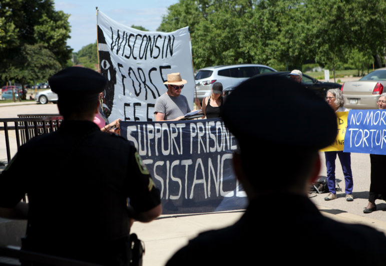 Ben Turk reads a list of demands and rule and policy changes that hunger strikers are seeking outside the state Department of Corrections headquarters in Madison, Wis. on July 5, 2016.  Protesters are trying to pressure the Wisconsin Department of Corrections to reduce use of solitary confinement including ending a form of indefinite isolation known as administrative confinement. Turk later presented the demands to Corrections spokesman Tristan Cook.