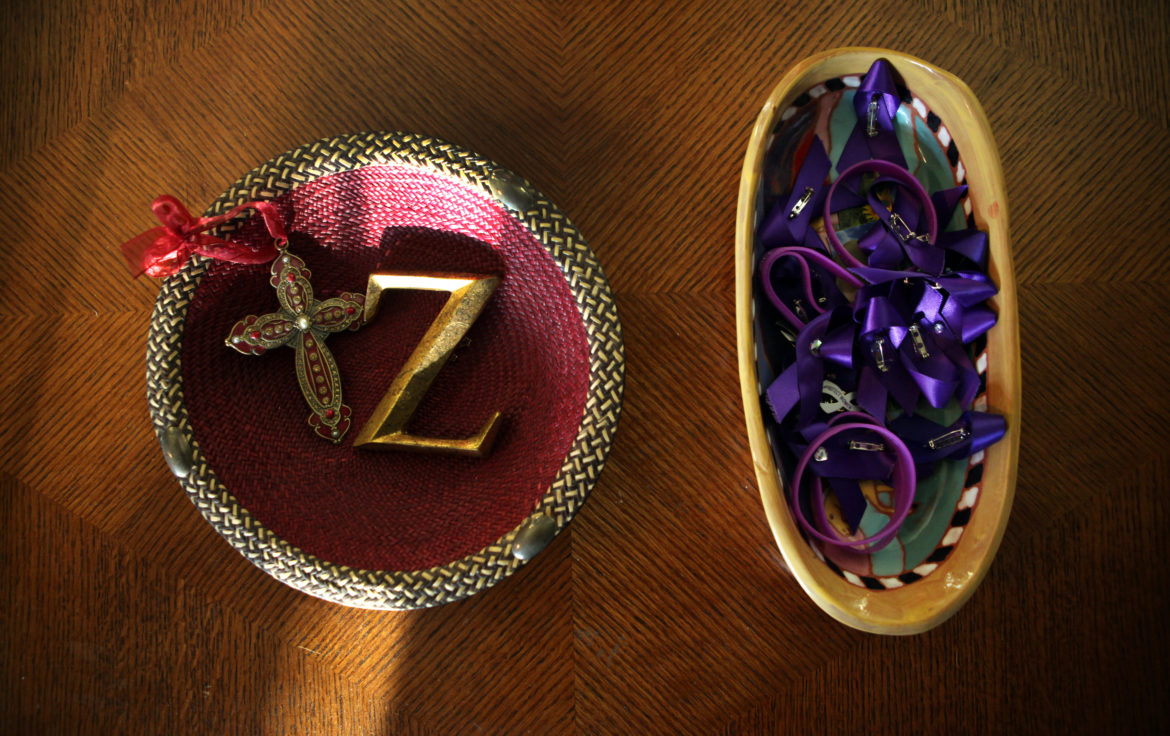 "Elvin and Cheryl Daniel keep a bowl on their coffee table with a cross, a ""Z,"" and a basket of ribbons and bracelets in Zina Haughton's favorite color, purple, to remember Elvin's slain sister. Haughton was murdered by her estranged husband with a gun he purchased via Armslist.com, despite having a restraining order against him."