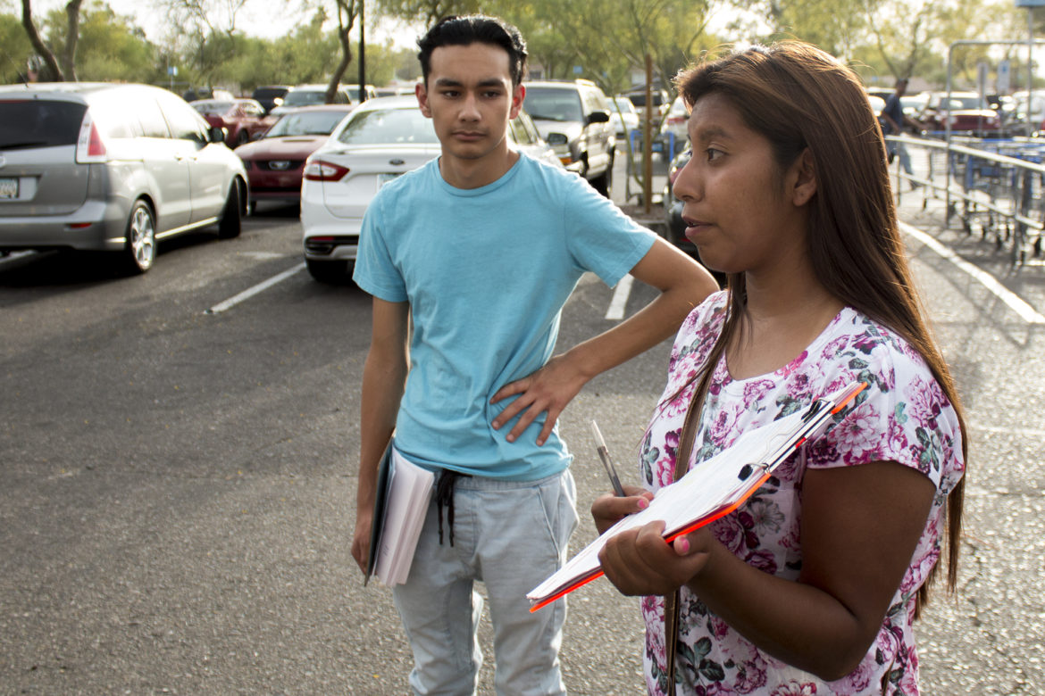 Yenni Sanchez, 18, has registered people to vote for three years. Daniel Flores, 16, is also a volunteer. They are signing up voters at a Wal-Mart parking lot in Phoenix.
