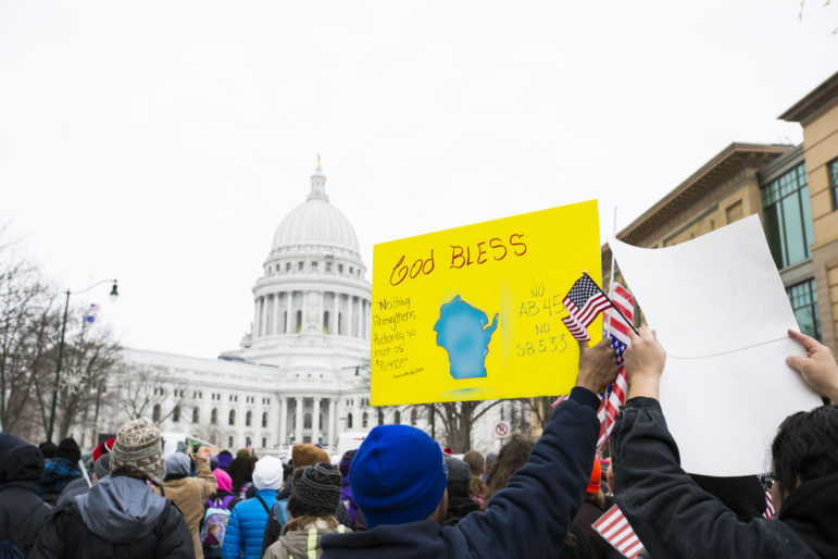 Latino protesters and supporters carry signs to the Capitol building to protest immigration bills on Feb. 18, 2016, Madison, Wis., including one that banned the use of city-issued identification to prove identity at the polls. Wisconsin is one of 20 states that has enacted new requirements for voting, including voter ID, 2012.