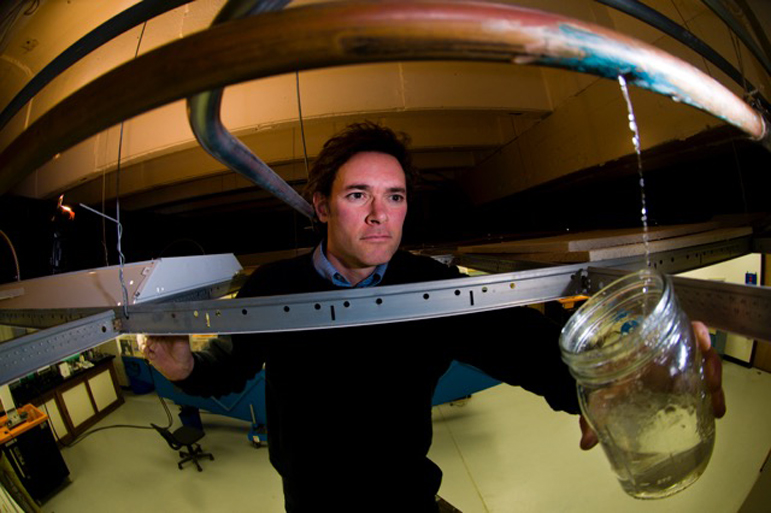 "Marc Edwards, a Virginia Tech engineering professor who is a national expert on lead in drinking water, collects a sample from a leaking water pipe. Edwards spoke Sept. 7, at a symposium in Milwaukee, saying the current federal law aimed at protecting the public from lead in drinking water is ""a total sick joke on the U.S. population."""