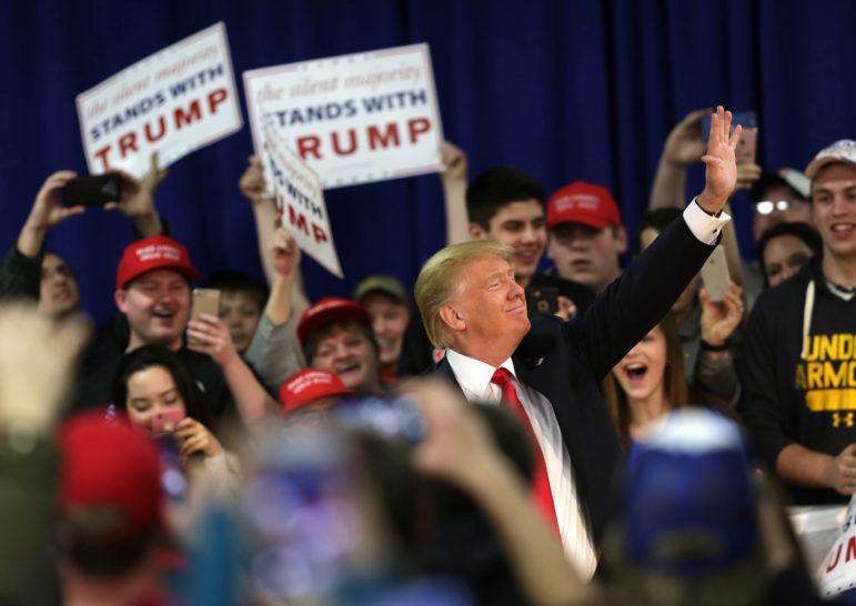 Donald Trump waves to fans after entering a town hall event in Rothschild, Wis., April 2, 2016.