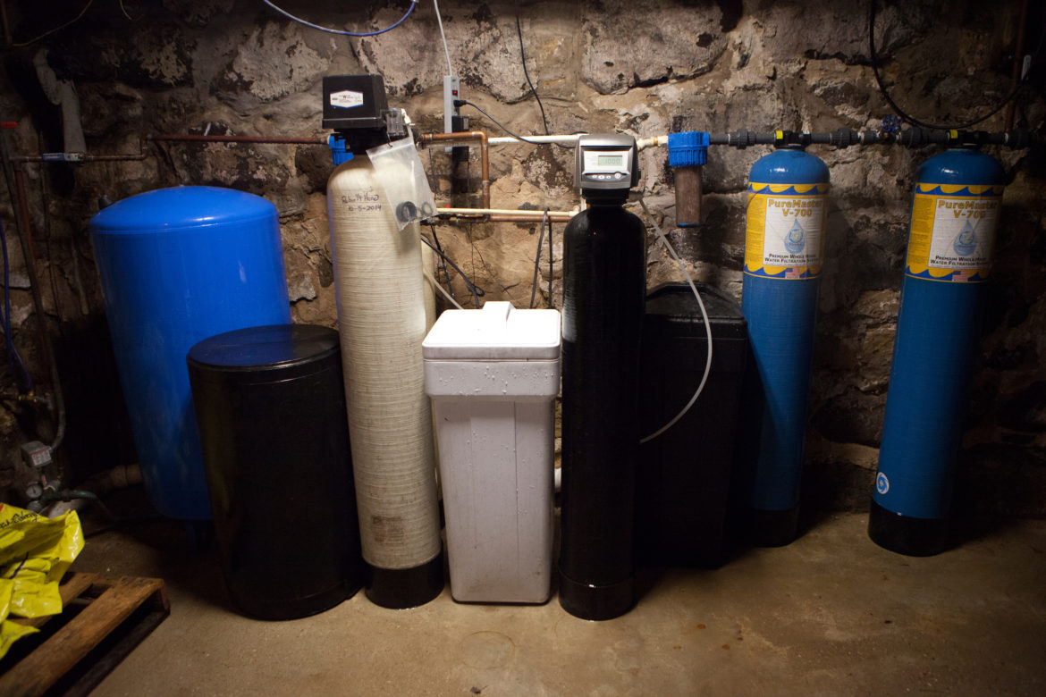 The water filtering system in the basement of Doug and Dawn Reeves' home shows the efforts the couple has made to remove atrazine and other contaminants from their drinking water. That includes the two small blue tanks that remove sediments, the black tank that removes nitrate, and the two large blue tanks that remove volatile organic compounds, herbicides and pesticides. The large blue filters cost the Reeves family $1,500 a piece. There also is a reverse osmosis filter attached to the kitchen faucet.