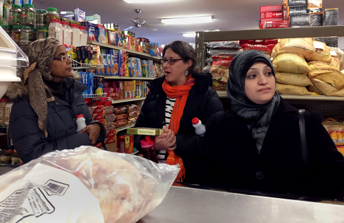 Rihab Taha, left, a caseworker for Jewish Social Services who came as an immigrant from Sudan; Becca Schwartz, resettlement coordinator for JSS; and Rula, a newly arrived refugee from Syria, shop at Istanbul Market in Madison, Wis., Jan. 31, 2017. Rula and her family came to Madison just one week before President Donald Trump indefinitely halted all refugee immigration from Syria.